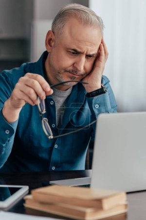 Photo for Selective focus of tired man looking at laptop while holding glasses - Royalty Free Image