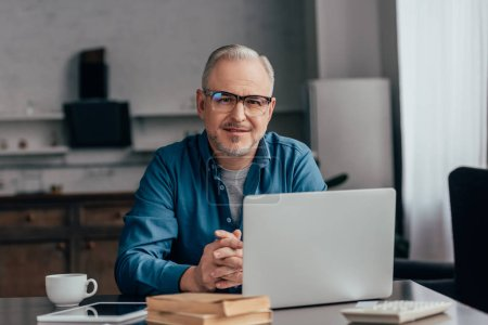 Photo for Cheerful man in glasses sitting near laptop at home - Royalty Free Image