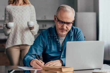 Photo for Selective focus of concentrated man in glasses writing near laptop with wife holding cups on background - Royalty Free Image