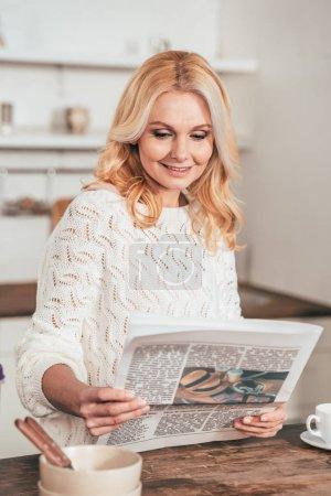 Photo pour Femme gaie lecture journal de voyage dans la cuisine - image libre de droit