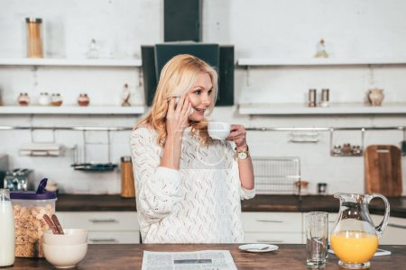 Photo for Cheerful woman talking on smartphone while drinking coffee in kitchen - Royalty Free Image