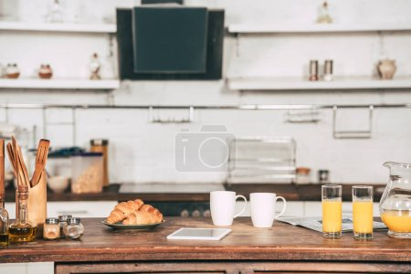 Photo for Cups with drinks near glasses with orange juice and digital tablet in kitchen - Royalty Free Image