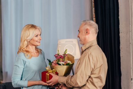 happy man giving flowers and gift box to beautiful wife at home