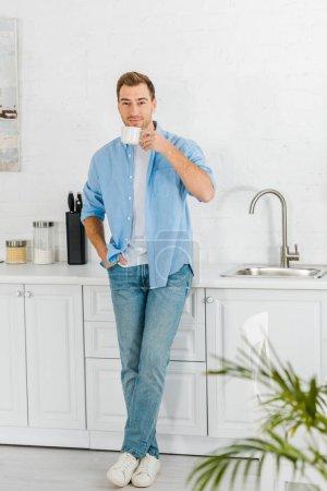 Photo pour Bel homme en regardant la caméra et de boire du café dans la cuisine, des vêtements décontractés - image libre de droit
