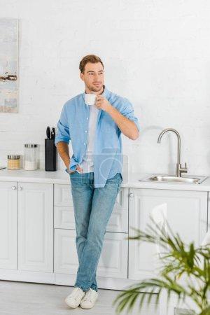 Photo pour Bel homme dans des vêtements décontractés, boire du café dans la cuisine - image libre de droit