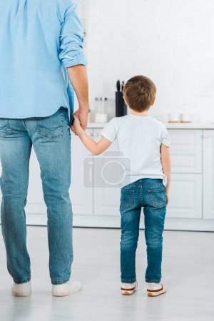 Photo for Back view of preschooler holding hands with father in kitchen - Royalty Free Image