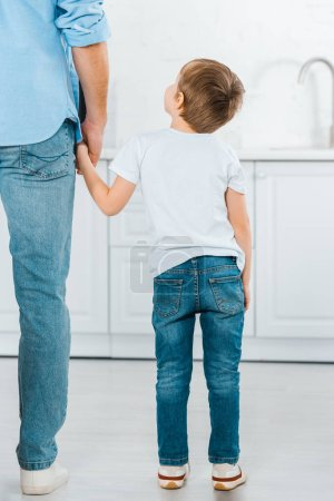 Photo for Back view of preschooler holding hands with father at home - Royalty Free Image