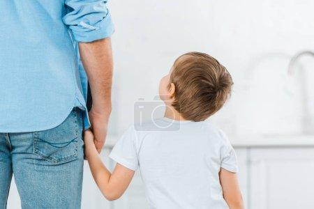 Foto de Vista posterior de preescolar cogidos de la mano con el padre en el hogar - Imagen libre de derechos