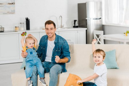 Photo for Happy father looking at camera while spending time and playing with cheering preschooler and toddler sons in apartment - Royalty Free Image