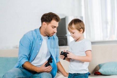 Foto de Padre con hijo preescolar con palancas de mando durante el juego de video en casa - Imagen libre de derechos