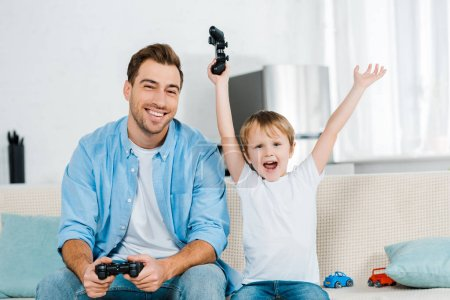 Photo for Preschooler son cheering with hands in air while playing video game with father at home - Royalty Free Image