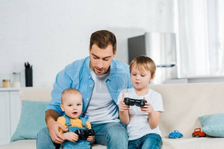 Photo for Father playing video game with preschooler and toddler sons while sitting on couch at home - Royalty Free Image