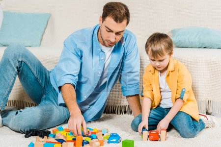 Photo for Father and preschooler son playing with colorful building blocks and toy cars at home - Royalty Free Image