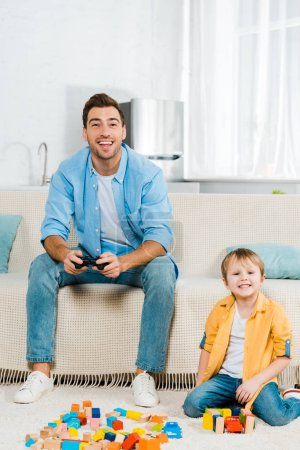 Foto de Hermoso padre sonriente jugando video juego mientras hijo lindo niño jugando con coloridos bloques de construcción en el país - Imagen libre de derechos