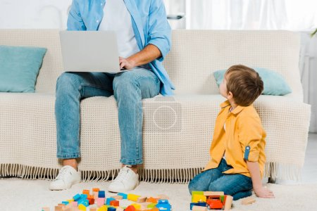 Photo for Father sitting on couch and using laptop while preschooler son playing with colorful building blocks at home - Royalty Free Image