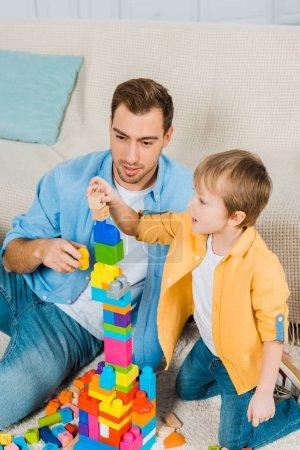 Photo pour Père et fils préscolaire jouer avec des blocs de construction colorés à la maison - image libre de droit