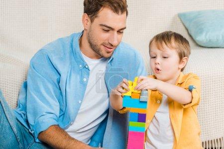 Foto de Padre e hijo adorable niño jugando con coloridos bloques de construcción en el país - Imagen libre de derechos