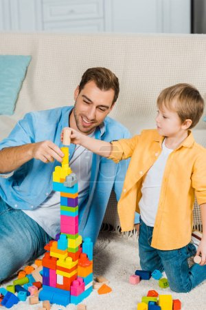 Photo for Smiling father and preschooler son playing with colorful building blocks at home - Royalty Free Image