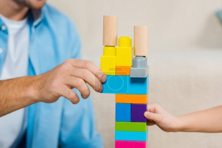 Photo for Cropped view of man and boy playing with building blocks - Royalty Free Image