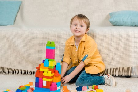 Photo for Adorable preschooler boy looking at camera while playing with colorful building blocks at home - Royalty Free Image