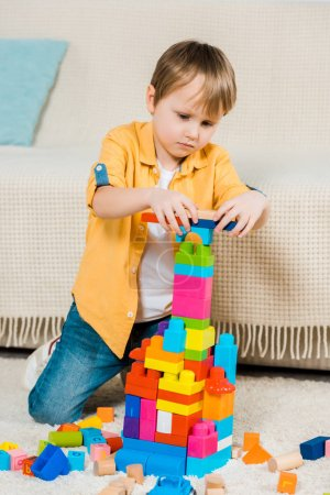 Photo for Adorable preschooler boy playing with colorful building blocks at home - Royalty Free Image
