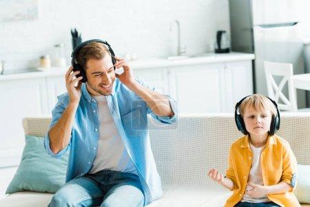 Photo pour Souriant père avec mignon fils préscolaire dans les écouteurs écouter de la musique à la maison - image libre de droit