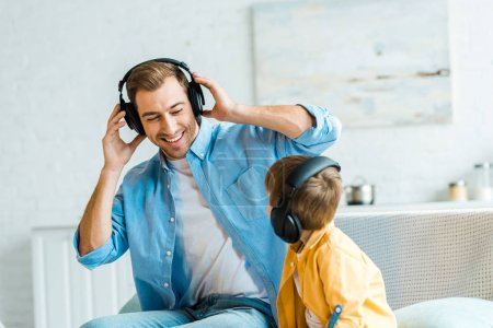 handsome smiling father with preschooler son in headphones listening music at home