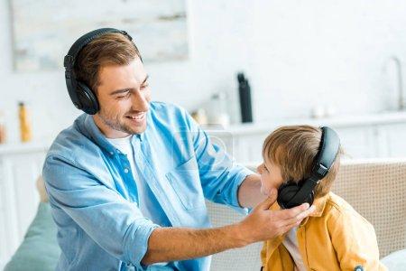 Photo pour Beau père souriant avec enfant d'âge préscolaire fils dans les écouteurs écouter de la musique à la maison - image libre de droit