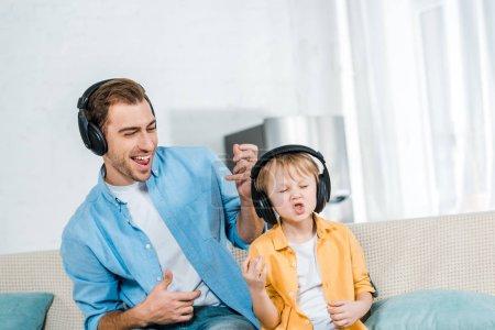 Photo pour Père avec enfant d'âge préscolaire fils dans les écouteurs écouter de la musique, geste avec les mains et jouer des guitares imaginaires à la maison - image libre de droit
