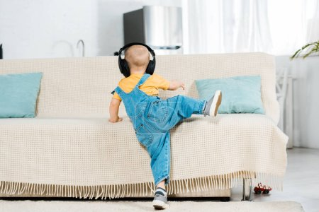 Photo for Back view of male toddler in headphones listening music and climbing on couch at home - Royalty Free Image