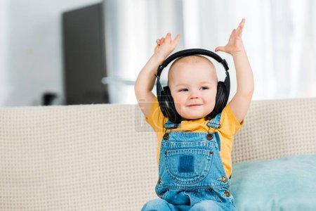 Photo pour Adorable mâle tout-petit dans les écouteurs avec les mains dans l'air écouter de la musique à la maison - image libre de droit