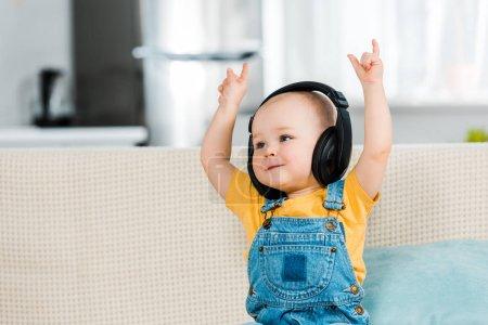 Photo pour Adorable mâle tout-petit dans les écouteurs écouter de la musique et montrer des signes rock à la maison - image libre de droit