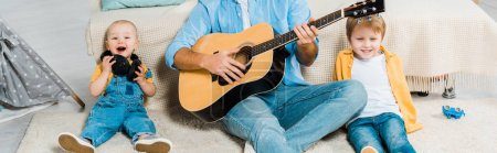 Photo for Father playing acoustic guitar to happy preschooler and toddler sons at home - Royalty Free Image