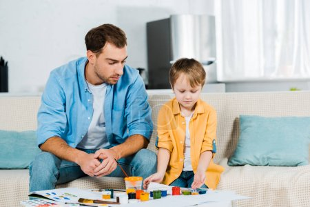 Photo for Father and preschooler son sitting with art supplies during drawing at home - Royalty Free Image