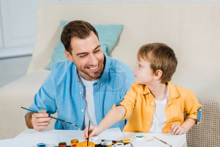 Photo for Happy father and preschooler son holding paintbrushes and drawing at home - Royalty Free Image