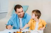 "Постер, картина, фотообои ""Счастливый отец и дошкольника сын Холдинг кисти и опираясь на дому"""