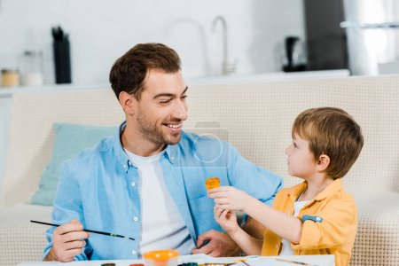 Photo for Handsome father and adorable preschooler son drawing at home - Royalty Free Image