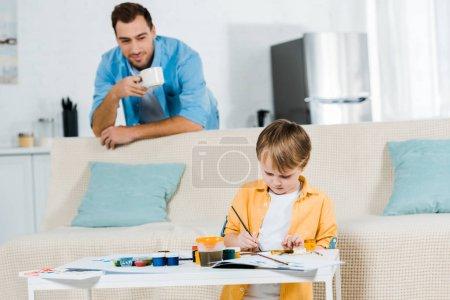 Foto de Hijo de preescolar sentados en sofá y dibujo en casa mientras el padre tomando café en el fondo - Imagen libre de derechos