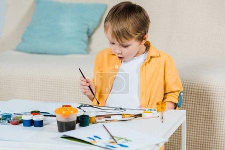 Photo pour Garçon surpris bambin mignon dessin avec un pinceau à la maison - image libre de droit