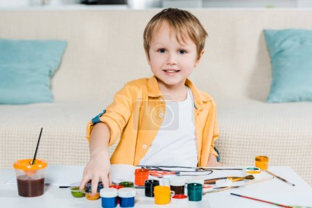 Photo for Adorable smiling preschooler boy looking at camera while drawing at home - Royalty Free Image