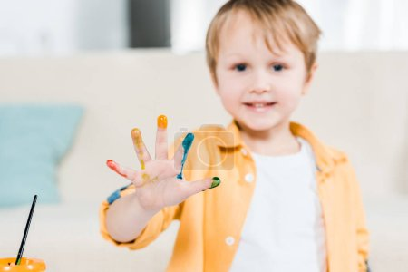 Photo for Cute preschooler boy with colorful paint on hand looking at camera at home - Royalty Free Image