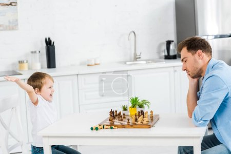Photo for Preschooler son cheering with hands in air while playing chess with father at home - Royalty Free Image