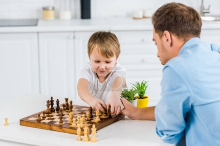 Photo for Father and preschooler son sitting at table and playing chess at home - Royalty Free Image