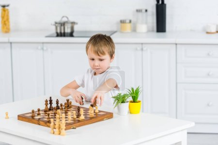 Photo for Adorable preschooler boy sitting at table and playing chess at home - Royalty Free Image