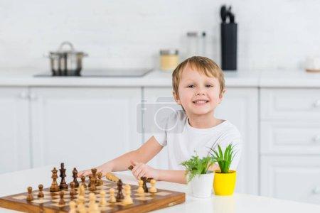 Photo pour Adorable garçon bambin souriant assis à table, regardant la caméra et de jouer aux échecs à la maison - image libre de droit