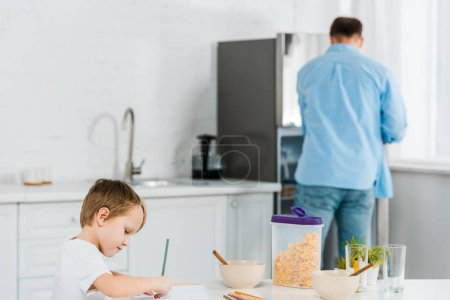 Photo for Preschooler son drawing during breakfast with father on background in kitchen - Royalty Free Image