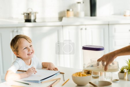 Photo for Happy preschooler son drawing while father pouring milk in bowl during breakfast in kitchen - Royalty Free Image