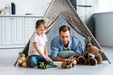 Foto de Hijo de padre y niño jugando con coches de juguete y los osos de peluche en wigwam en casa - Imagen libre de derechos