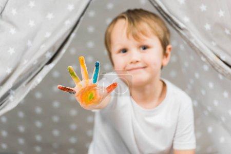 Photo pour Garçon mignon bambin avec peinture colorée sur la main, regardant la caméra à la maison - image libre de droit