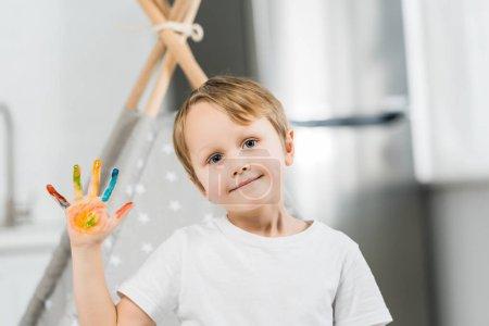 Photo pour Adorable garçon préscolaire souriant avec de la peinture colorée à portée de main regardant la caméra à la maison - image libre de droit